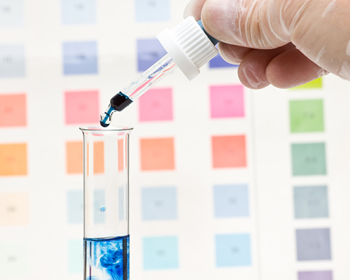Water test in a tube with PH chart in the background